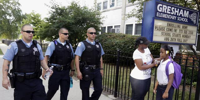 "FILE - In this Aug. 26. 2013, file photo, Chicago Police patrol the neighborhood at Gresham Elementary School on the first day of classes in Chicago. Thanks to $1 million from the city, another 100 ""Safe Passage"" workers will be on routes kids walk through crime-ridden neighborhoods when classes resume Tuesday, Sept. 2, 2014. (AP Photos/M. Spencer Green, File)"