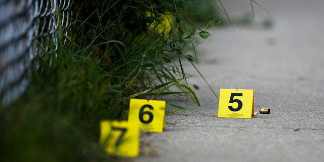In this Sunday, Aug. 5, 2018 photo, evidence markers sit on the ground at the scene where a boy was killed after being shot in the abdomen while riding his bike in Chicago.