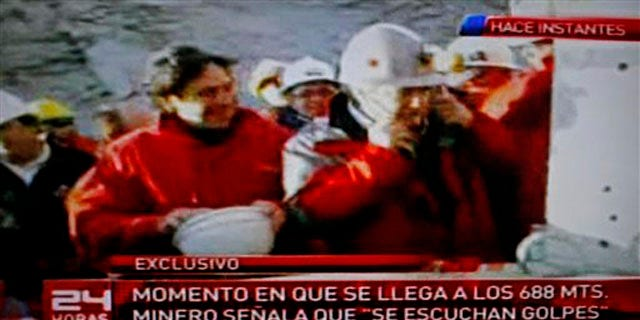 Aug. 22: Chile's Mining Minister Laurence Golborne, left, smiles as an unidentified official listens with a medical oscilloscope to unknown sounds coming from the area of a collapsed mine where about 33 miners have been trapped for 17 days in Copiapo, Chile, on Sunday.