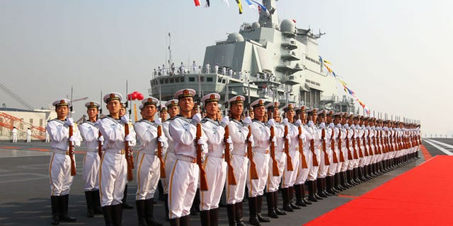 """Sept. 25, 2012: Military officers stand onboard China's aircraft carrier """"Liaoning"""" in Dalian, northeast China's Liaoning Province, as the country formally entered its first aircraft carrier into service."""