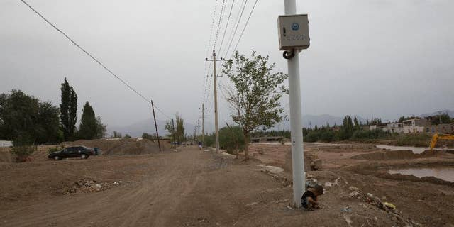 In this photo taken Wednesday, July 16, 2014, a child plays under police surveillance cameras set up to monitor a dirt road intersection in Kuqa in western China's Xinjiang province. (AP Photo/Ng Han Guan)