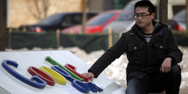 A Chinese man shuts his eyes briefly as he places a hand on the Google logo outside the Google China headquarters in Beijing.
