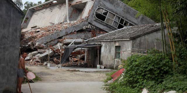 July 16, 2014: A man stands near the razed remains of a Catholic church in a village in Pingyang county of Wenzhou in eastern China's Zhejiang province.