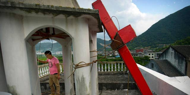 Lay leader Tu Shouzhe stands on his Protestant church's roof hours after Chinese government workers came and cut down the building's cross.