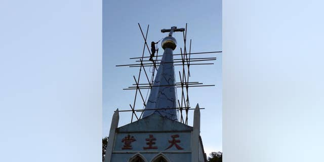 A cross atop the Lower Dafei Catholic Church topples after being cut down by a Chinese government worker with a cutting torch.