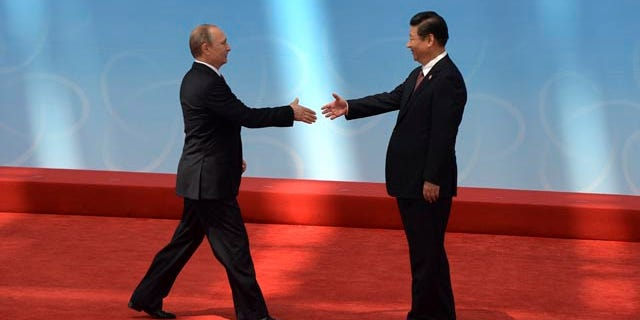 May 21, 2014: Russian President Vladimir Putin, left, is greeted by Chinese President Xi Jinping before the opening ceremony at the fourth Conference on Interaction and Confidence Building Measures in Asia (CICA) summit, in Shanghai. (AP Photo/Mark Ralston, Pool)