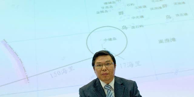 May 8, 2014: Yi Xianliang, deputy director-general of Chinese Ministry of Foreign Affairs' Department of Boundary and Ocean Affairs, stands up, in front of a map showing a disputed zone in South China Sea, to leave a press conference in Beijing, China.