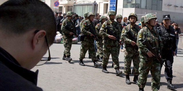 May 1, 2014: Heavily armed Chinese paramilitary policemen march past the site of Wednesday's explosion outside the Urumqi South Railway Station in Urumqi in northwest China's Xinjiang Uygur Autonomous Region. (AP Photo/Ng Han Guan)