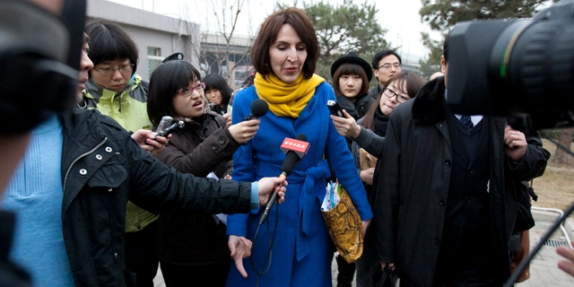 """March 22, 2012: Kim Lee, center, wife of """"Crazy English"""" founder Li Yang, is surrounded by local journalists as she walks into a court for her divorce trial in Beijing, China."""