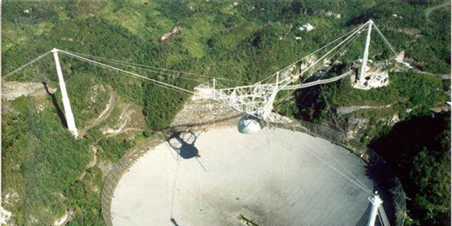 China's soon-to-be-completed FAST radio telescope will dwarf the Arecibo radio telescope in Puerto Rico, shown here. The Chinese government is forcing more than 9,000 people from their homes to make room for it.