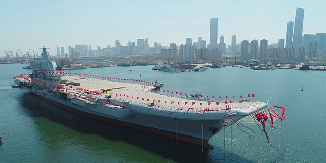 In this April 26, 2017, file photo released by China's Xinhua News Agency, China's newly-built aircraft carrier Liaoning is transferred from dry dock into the water at a launch ceremony at a shipyard in Dalian.