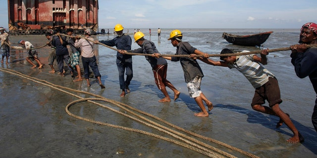 Workers haul a ship to shore for salvage at a ship-breaking yard in Chittagong, Bangladesh.