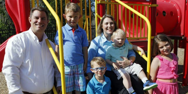 In this May 29, 2014 photo, Christy Wolford holds her youngest son Lucas, 2, as her husband Bubba and other children Lauren, 8, Alexander, 4, and Everett, 3, are pictured at the Primrose School the couple runs in Fort Collins, Colo. Christy Wolford's ovaries were suppressed during cancer treatment and she has had three boys since it ended in 2006. (AP Photo/Ed Andrieski)