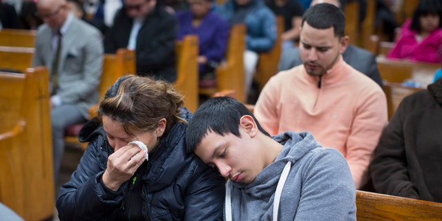 Parishioners mourn during Sunday services at the Church of God of Third Avenue as the congregation welcomed members of the Spanish Christian Church that was destroyed by Wednesday's explosion in the East Harlem neighborhood of New York, Sunday, March 16, 2014. The Spanish Christian Church had been located on the first floor of one of the destroyed buildings. On Saturday a crew at the blast site found a large Bible in the rubble and returned it to the church's pastor. (AP Photo/John Minchillo)