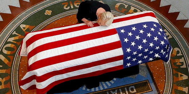 Cindy McCain, wife of Sen. John McCain, R-Ariz., lays her head on casket during a memorial service at the Arizona Capitol on Wednesday in Phoenix.