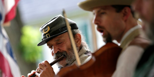 In this June 16, 2012 photo, Greg Hernandez plays a fife during a performance with the 2nd South Carolina String Band in Hagerstown, Md. Some re-enactors have formed camp bands to play music that soldiers enjoyed hearing around battlefield campfires. The most popular tunes included songs from the minstrel stage. Groups such as the 2nd South Carolina String Band pride themselves on their accurate impressions  right down to the exaggerated black dialect of songs with inescapably racist overtones. (AP Photo/Patrick Semansky)