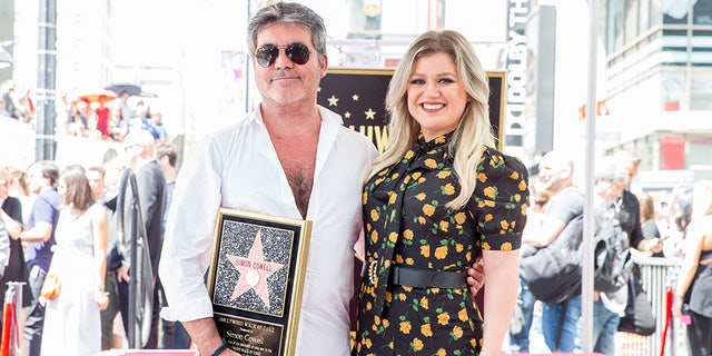 Simon Cowell and Kelly Clarkson attend a ceremony honoring Cowell with a star on the Hollywood Walk of Fame on August 22, 2018.