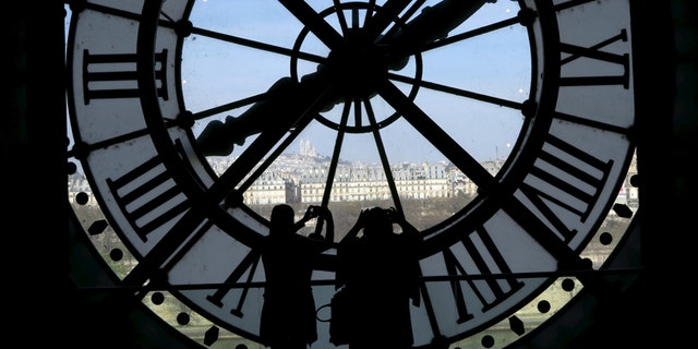File photo - Visitors at the Musee d'Orsay are seen in silhouette as they take pictures from behind a giant clock face April 8, 2015.