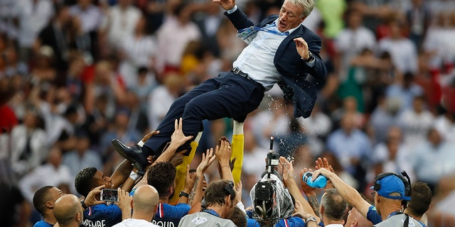 France's head coach Didier Deschamps thrown into the air by his players as they celebrated.