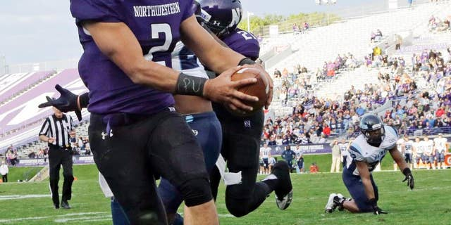 """FILE - In this Sept. 21, 2013, file photo, Northwestern quarterback Kain Colter (2), wears APU for """"All Players United"""" on wrist tape as he scores a touchdown during an NCAA college football game against Maine in Evanston, Ill. The five-member regulatory board that will ultimately decide if Northwestern University football players can unionize has itself been in the middle of a firestorm. The very makeup of the National Labor Relations Board has been challenged in a case now before the Supreme Court. And Republicans contend the agency has being overly friendly to organized labor.  (AP Photo/Nam Y. Huh, File)"""