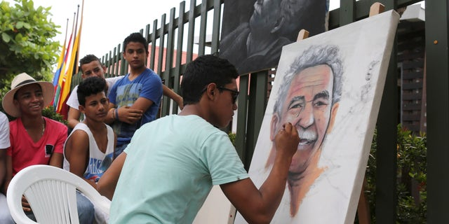 Melquin Merchan paints a portrait of 'Gabo' in front of the house where he was born in Aracataca, Colombia.
