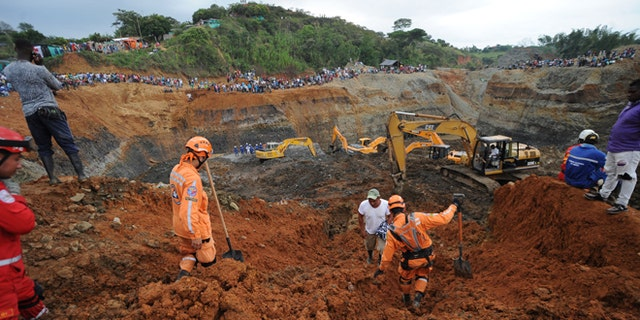 People watch for the search of survivors at a collapsed illegal gold mine in Santander de Quilichao, southern Colombia, Thursday, May 1, 2014.  Colombian rescuers on Thursday hunted for more than a dozen people feared trapped beneath debris left by in the collapse of an illegal gold mine that killed at least three people, officials said. (AP Photo/Oswaldo Paez, El Pais)