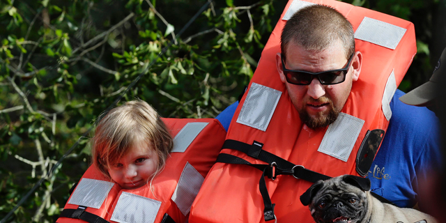 Brent Lamb, right, and his daughter Laci, 4, are removed from a flooded neighborhood by members of the U.S. Coast Guard Shallow Water Rescue Team in Lumberton, N.C., Monday, Sept. 17, 2018, following flooding from Hurricane Florence. (AP Photo/Gerry Broome)