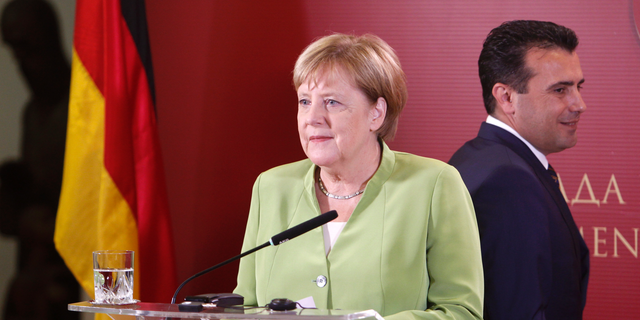 German Chancellor Angela Merkel and Macedonian Prime Minister Zoran Zaev, right, arrive for a news conference following their talks at the government building in Skopje, Macedonia, Saturday, Sept. 8, 2018. German chancellor Angela Merkel is a third western leader this week who has urged Macedonians to back massively the referendum on a deal with neighboring Greece aimed at ending a decades-old name dispute. (AP Photo/Boris Grdanoski)