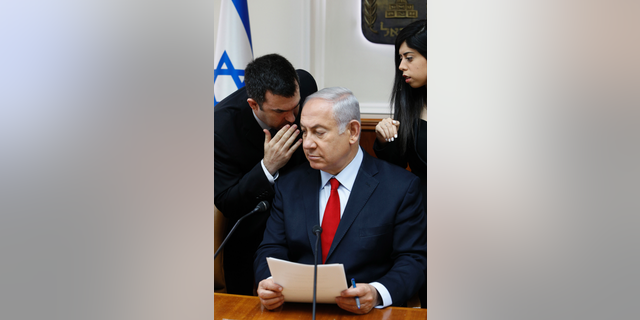 FILE - In this July 23, 2018 file photo, Israeli Prime Minister Benjamin Netanyahu listens to his spokesman David Keyes as he opens the weekly cabinet meeting at his Jerusalem office. An opposition Israeli lawmaker is calling on Netanyahu to suspend Keyes following sexual assault allegations. Michal Rozin, a legislator with the dovish Meretz party, says David Keyes, Netanyahu's spokesman to the foreign media, can no longer represent Israel to the world amid the accusations. (Gali Tibbon/Pool via AP, File)