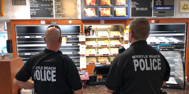 Two police officers get ready to order at Joseph Santos' Donut Man restaurant in Myrtle Beach, S.C., on Friday, Sept. 14, 2018. Santos says he keeps his restaurant open to feed police officers, firefighters and others who have to work no matter what. (AP Photo/Jeffrey Collins)