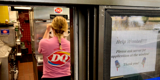 """FILE - In this Sunday, Aug. 19, 2018, file photo a woman prepares a cup of ice cream behind a """"Help Wanted"""" sign at a Dairy Queen fast food restaurant in Rutherford, N.J. On Tuesday, Sept. 11, the Labor Department reports on job openings and labor turnover for July. (AP Photo/Ted Shaffrey, File)"""