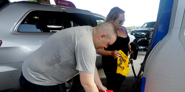 "Sarah Dankanich, right, removes an ""out of service"" wrapper from a gas pump as her husband, Bryan Dankanich, left, prepares to pump gas in cans in advance of Hurricane Florence in Wilmington, N.C., Wednesday, Sept. 12, 2018. Florence exploded into a potentially catastrophic hurricane Monday as it closed in on North and South Carolina, carrying winds up to 140 mph (220 kph) and water that could wreak havoc over a wide stretch of the eastern United States later this week. (AP Photo/Chuck Burton)"
