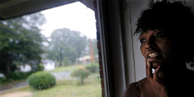 """Nichole Worley looks out from her home in Lumberton, N.C., Friday, Sept. 14, 2018, as rains from Hurricane Florence threaten the neighborhood with flooding. Two years ago, Worley's house, and most of the houses around her, took in water up to its eaves during Hurricane Matthew. """"I don't think we can stand another one,"""" she says. """"I can't do this again."""" (AP Photo/David Goldman)"""