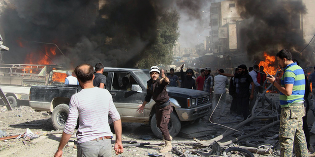 FILE - This file photo provided Sunday, Oct. 8, 2017 by the Syrian Civil Defense White Helmets, which has been authenticated based on its contents and other AP reporting, shows Civil Defense workers and Syrian citizens gathering after an airstrike hit a market in Maaret al-Numan in southern Idlib, Syria. When the presidents of Russia, Turkey and Iran meet in Tehran on Friday, Sept. 7, all eyes will be on their diplomacy averting a bloodbath in Idlib, Syria's crowded northwestern province and last opposition stronghold. The three leaders whose nations are all under U.S. sanctions have an interest in working together, but Idlib is complicated and they have little common ground. (Syrian Civil Defense White Helmets via AP, File)