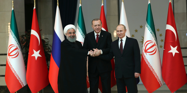 FILE- In this April 4, 2018, file photo, Iran's President Hassan Rouhani, left, Russia's President Vladimir Putin, right, and Turkey's President Recep Tayyip Erdogan lock hands during a group photo in Ankara, Turkey. When the presidents of Russia, Turkey and Iran meet in Tehran Friday, Sept. 7, all eyes will be on their diplomacy averting a bloodbath in Idlib, Syria's crowded northwestern province and last opposition stronghold. The three leaders whose nations are all under U.S. sanctions have an interest in working together, but Idlib is complicated and they have little common ground. (Tolga Bozoglu/Pool Photo via AP, File)