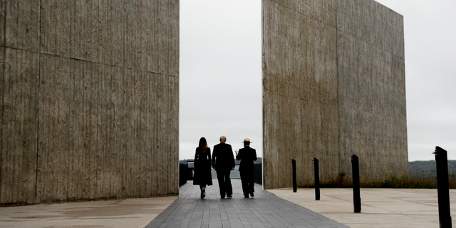 "In this Sept. 11, 2018, photo, President Donald Trump and first lady Melania Trump, escorted by Stephen Clark, Superintendent of the National Parks of Western Pennsylvania, walk along the September 11th Flight 93 memorial in Shanksville, Pa. Trump says the Sept. 11 memorial in Shanksville renewed his resolve to push for his stalled southern border wall. Trump tells Hill.TV in an interview published Sept. 19 that he marveled at the Flight 93 National Memorial during a visit. Trump says, ""They built this gorgeous wall where the plane went down."" He says, ""What they did is incredible,"" adding: ""They have a series of walls, I'm saying, it's like perfect. So, so, we are pushing very hard."" (AP Photo/Evan Vucci)"
