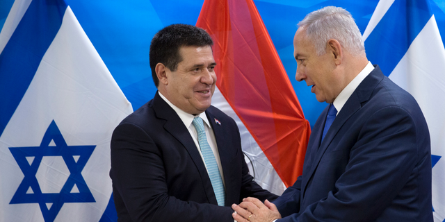 FILE - In this May 21, 2018 file photo, Israeli Prime Minister Benjamin Netanyahu, right, speaks with Paraguay's President Horacio Cartes during their meeting at the Prime Minister's office in Jerusalem. Paraguay's government says it's moving its embassy in Israel out of Jerusalem and back to Tel Aviv, less than four months after opening the new mission, Foreign Minister Luis Alberto Castiglioni announced Wednesday, Sept. 5, 2018. (AP Photo/Sebastian Scheiner, Pool, File)