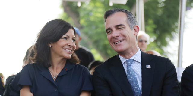 Paris Mayor Anne Hidalgo and Los Angeles Mayor Eric Garcetti speaks during a ceremony marking the 17th anniversary of the Sept. 11, 2001 terrorist attacks on America, at the Los Angeles Fire Department's training center Tuesday, Sept. 11, 2018. The mayors of Paris and Los Angeles met Tuesday ahead of a global climate summit to memorialize the victims of the 9/11 attacks on the U.S., and to talk about the commonalities between the two cities amid an increasingly divided world. The mayors then helped pack lunches for the needy. (AP Photo/Reed Saxon)