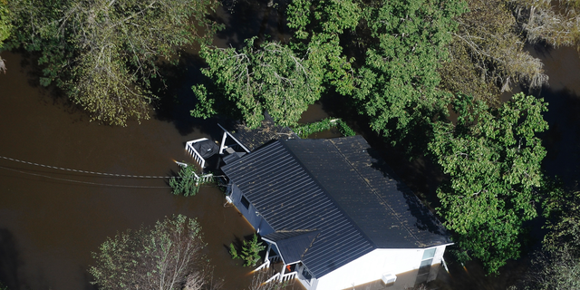 FILE-In this Monday, Oct. 10, 2016 file photo, a home sits in flood waters in Nichols, S.C. The residents of a tiny town in South Carolina who rebuilt after an inland flood from a hurricane destroyed 90 percent of the homes two years ago are uneasy as forecasters warn inland flooding from Hurricane Florence's rain could be one of the most dangerous and devastating parts of the storm. (AP Photo/Rainier Ehrhardt, File)