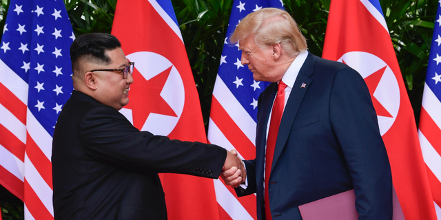 FILE - In this June 12, 2018 file photo, North Korea leader Kim Jong Un and U.S. President Donald Trump shake hands at the conclusion of their meetings at the Capella resort on Sentosa Island in Singapore. The newly appointed U.S. special envoy for North Korea will make his first diplomatic trip abroad next week in the Trump administration's latest effort to press for progress in uncertain denuclearization talks. (AP Photo/Susan Walsh, Pool)