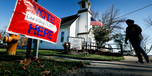 FILE - In this Tuesday, Nov. 8, 2016 file photo, a local resident leaves a church after voting in the general election in Cumming, Iowa. Religion's role in politics and social policies is in the spotlight heading toward the midterm elections, yet relatively few Americans consider it crucial that a candidate be devoutly religious or share their religious beliefs, according to an AP-NORC national poll conducted Aug. 16-20, 2018. (AP Photo/Charlie Neibergall)