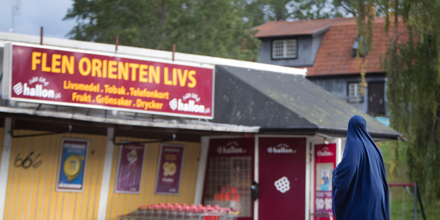 In this Aug. 30, 2018 photo a migrant woman stands in front of an orient supermarket in Flen, some 100 km west of Stockholm, Sweden. The town has welcomed so many asylum seekers in recent years that they now make up about a fourth of the population.  (AP Photo/Michael Probst)