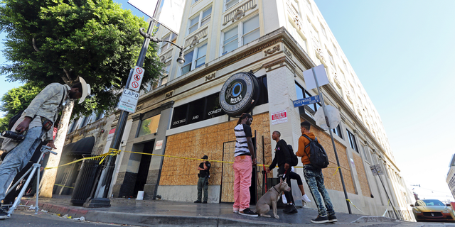 People who may have been occupants and others stand around a four-story vacant commercial building in Los Angeles' Hollywood district that was raided early in the morning of Wednesday, Sept. 12, 2018. Los Angeles police say more than 60 adults and at least four juveniles were detained during the raid where some people had been squatting. A search warrant was served before dawn on Hollywood Boulevard and officers went through the building, room by room, over several hours. Two firearms — a shotgun and a rifle— and drugs were seized, officials said. (AP Photo/Reed Saxon)