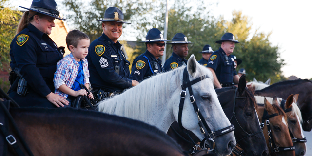 Kevin Will Jr., 5, the son of slain Houston police officer Kevin Will, sits on top of a horse as he is escorted to his first day of school by Houston police and other officers Tuesday, Aug. 22, 2017 in Cypress, Texas.