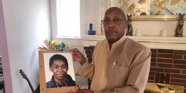 FILE - In this Sept. 5, 2018 file photo, Dia Khafra, father of Askia Khafra, holds a photo of his son in his Silver Springs, Md., home. The parents of 21-year-old Askia Khafra sued 27-year-old Daniel Beckwitt and his father on Monday, Sept. 10, 2018, the anniversary of the fire that killed Khafra in the basement of the Beckwitts' house in Bethesda, Maryland.  (AP Photo/Michael Kunzelman)