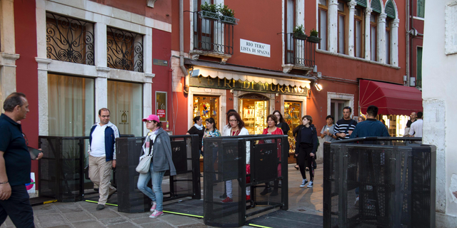 In this photo taken on Friday, April 27, 2018, people walk through gates in Venice, Italy.