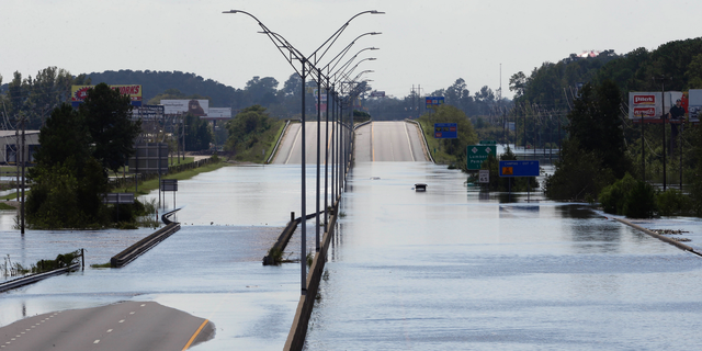 FILE- In this Monday, Sept. 17, 2018, file photo flooded vehicles sit on a closed section of Interstate 95 in Lumberton, N.C., where the Lumber river overflowed following flooding from Hurricane Florence. Navigation apps like Waze are trying to help motorists avoid hurricane flooding, but local authorities say people shouldn't rely on them. (AP Photo/Gerry Broome, File)