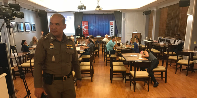 """In this Thursday, Sept. 6, 2018, photo, a Thai policeman stands inside Foreign Correspondents' Club of Thailand during an event titled: """"Will Myanmar's General Ever Face Justice for International Crimes"""" in Bangkok, Thailand. Police shut down a forum organized by foreign journalists to discuss whether senior military officers in Myanmar should face justice for alleged human rights abuses committed by their forces against Rohingya Muslims and other ethnic minorities. (AP Photo/Tassanee Vejpongsa)"""