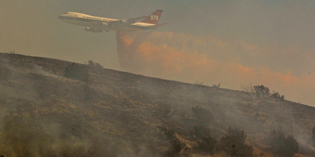 FILE - In this July 30, 2010, file photo, a Boeing Evergreen B-747 Supertanker drops fire retardant over a hillside subdivision on the outskirts of Palmdale, Calif. A report released Friday, Sept. 14, 2018, by California's firefighting agency says firefighter Mathew Burchett was killed on Aug. 13, by a tree uprooted when thousands of gallons of flame-suppressing liquid were dropped from a similar Boeing 747 flying only 100 feet above the treetops at the Mendocino Complex fire north of San Francisco. (AP Photo/Damian Dovarganes, File)