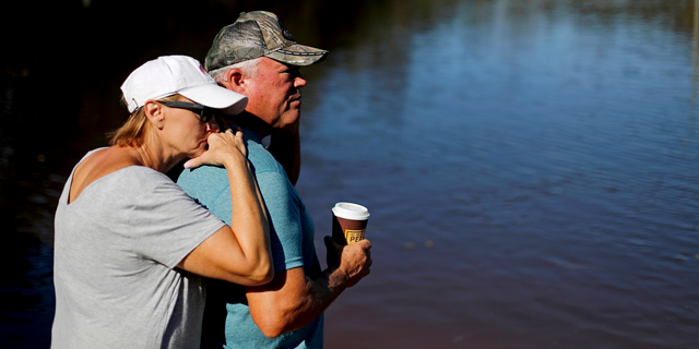"""Dianna Wood, left, embraces her husband Lynn, as they look out over their flooded property as the Little River continues to rise in the aftermath of Hurricane Florence in Linden, N.C., Tuesday, Sept. 18, 2018. """"I'm still hopeful,"""" said Lynn about his home which currently has water up to the front step. """"In another foot, I'll be heartbroken,"""" he added. (AP Photo/David Goldman)"""